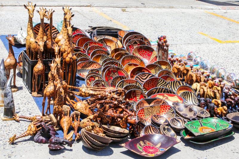Den traditionella lokala afrikanska souvenirmarknaden på gatan med rader av den sned handen målade träbunkar, giraff, elefanter m fotografering för bildbyråer