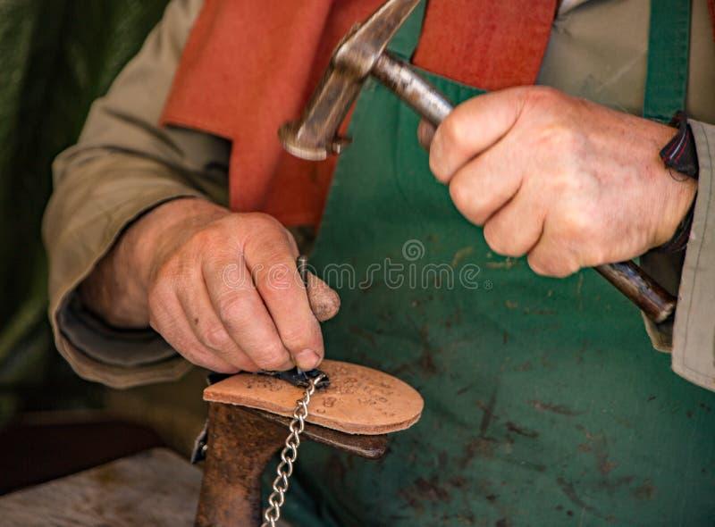 Den traditionella skotillverkaren arbetar på hälmellanlägget arkivfoton