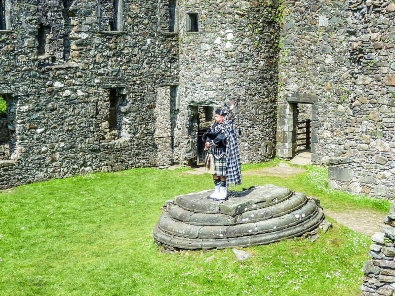 Den traditionella skotska säckpipeblåsaren på fördärvar av den Kilchurn slotten arkivbilder
