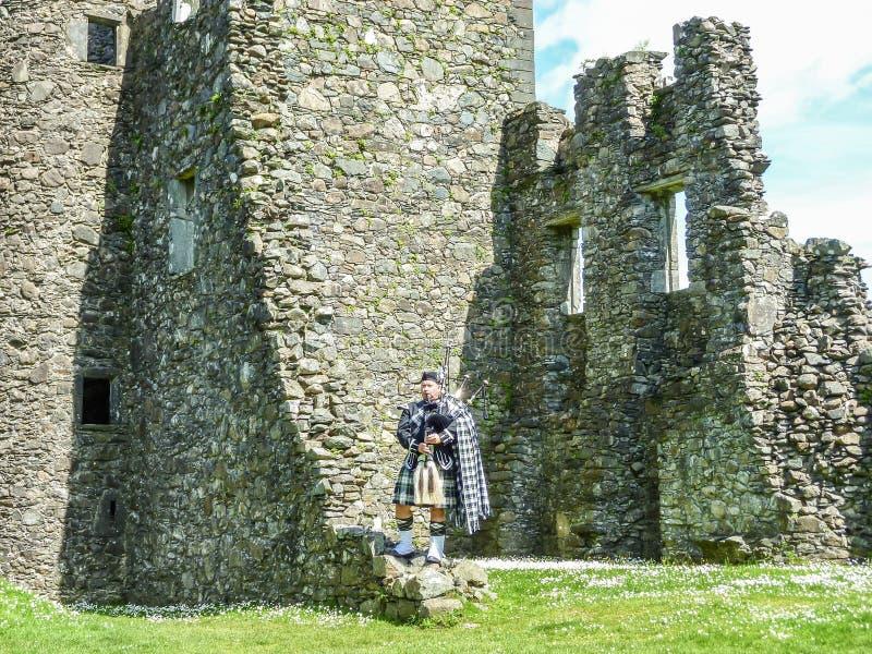 Den traditionella skotska säckpipeblåsaren på fördärvar av den Kilchurn slotten royaltyfri bild