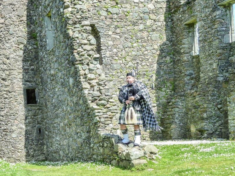 Den traditionella skotska säckpipeblåsaren på fördärvar av den Kilchurn slotten arkivfoto