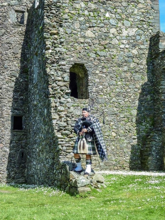 Den traditionella skotska säckpipeblåsaren på fördärvar av den Kilchurn slotten royaltyfri foto