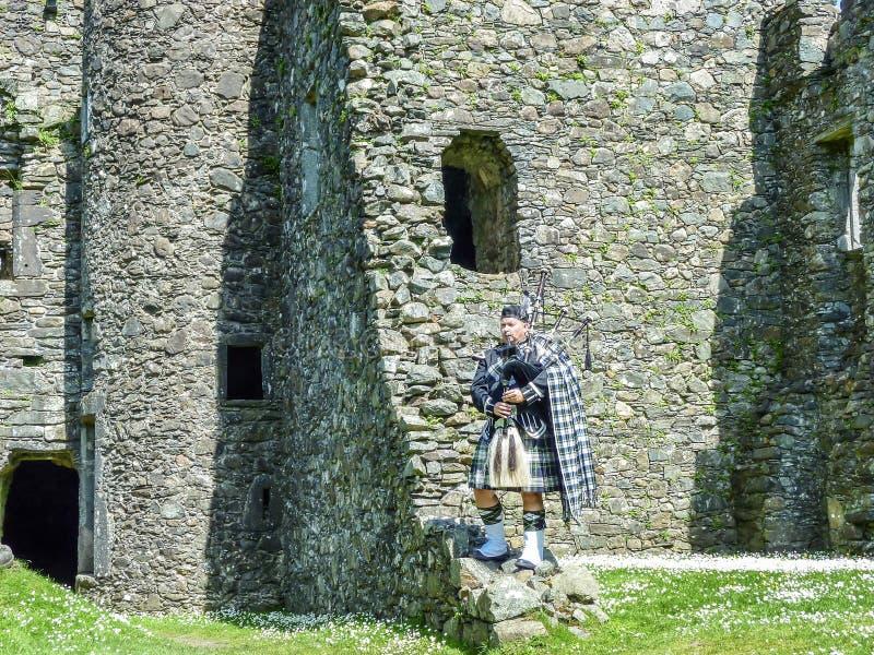 Den traditionella skotska säckpipeblåsaren på fördärvar av den Kilchurn slotten royaltyfria bilder