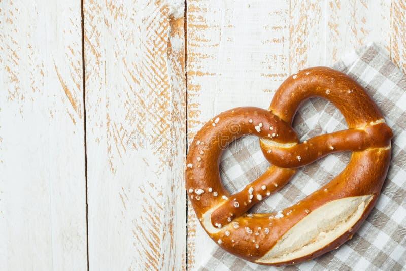 Den traditionella tyska välsmakande lutkringlan med saltar på den rutiga bomullskökshandduken på den vita plankaträtabellen Affis royaltyfri foto
