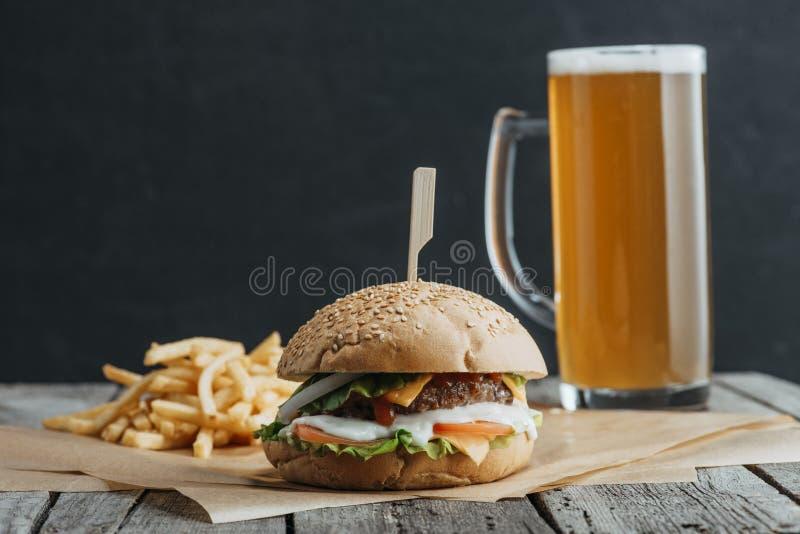 den traditionellt hemlagat hamburgaren, fransmansmåfiskar och exponeringsglas av öl på bakning skyler över brister royaltyfria foton
