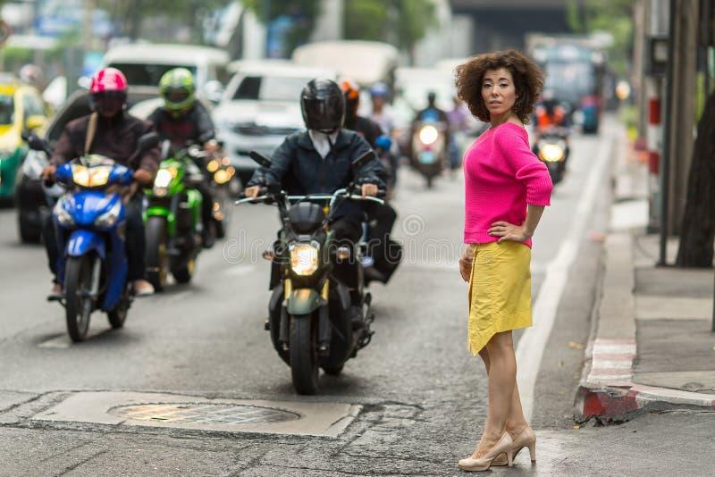 Den trendiga asiatiska kvinnan står nära en upptagen stadshuvudväg arkivfoto