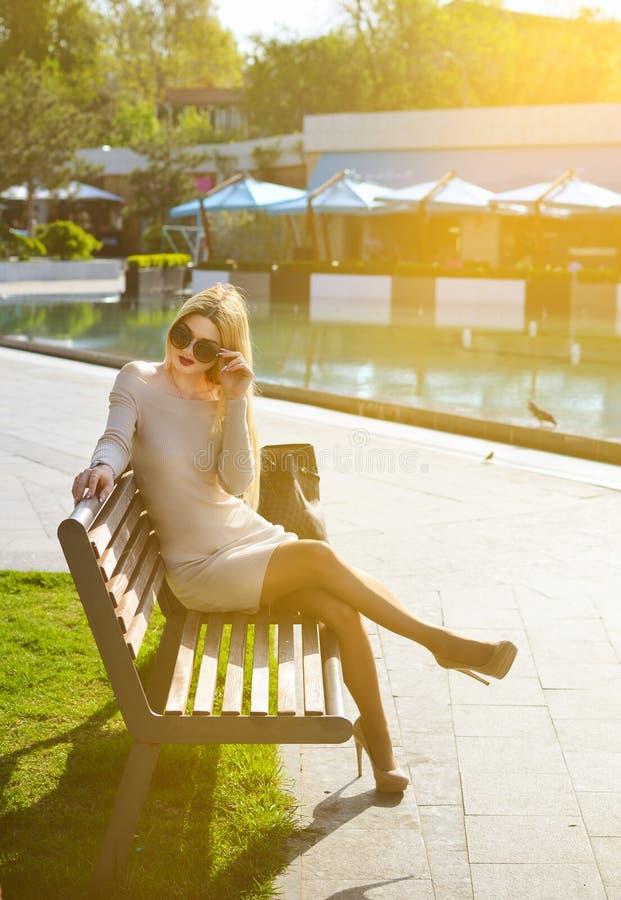 Den trendiga blonda flickan i en klänning och solglasögon sitter på en bänk Begreppet av ett lyxigt liv arkivfoto