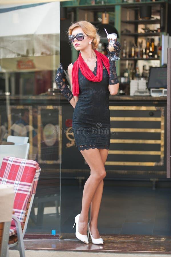 Den trendiga damen med kort svart snör åt klänningen och röda höga häl för halsduk och, utomhus- skott Ung attraktiv kort haired  arkivfoto