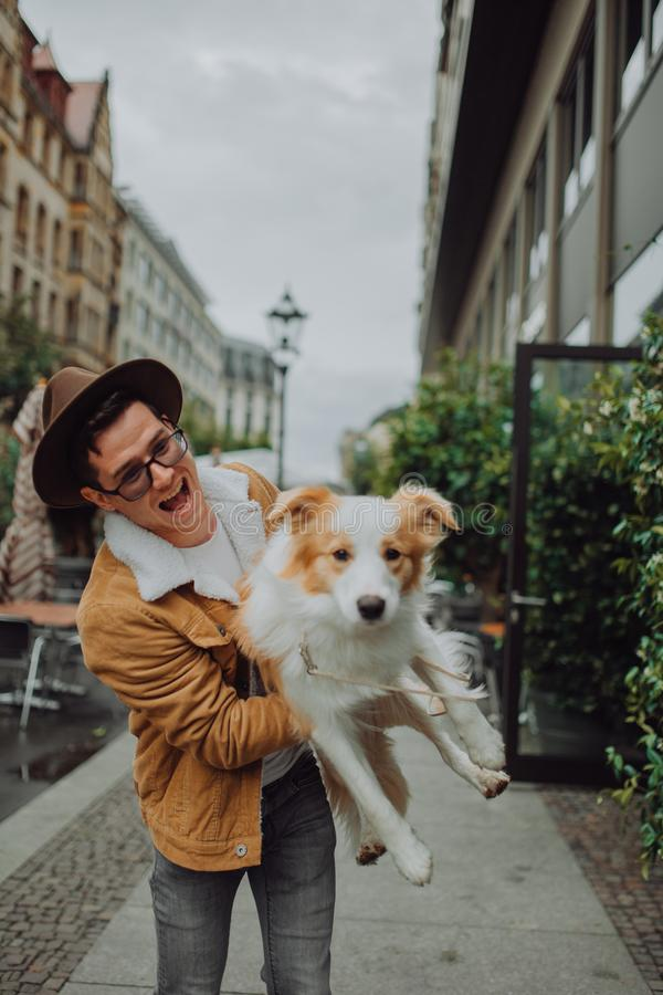 Den trendiga grabben i en hatt går runt om Europa i staden med hans röda hund border collie royaltyfri bild