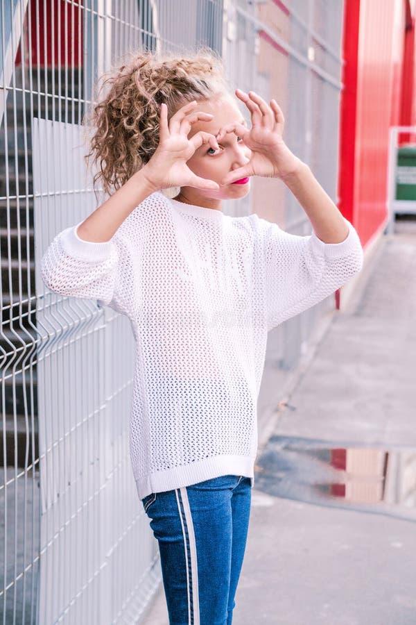 Den trendiga härliga flickan visar hjärtahandtecknet royaltyfri fotografi