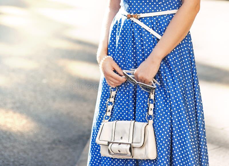 Den trendiga kvinnan med den vita påsen i henne händer och blått klär royaltyfria bilder
