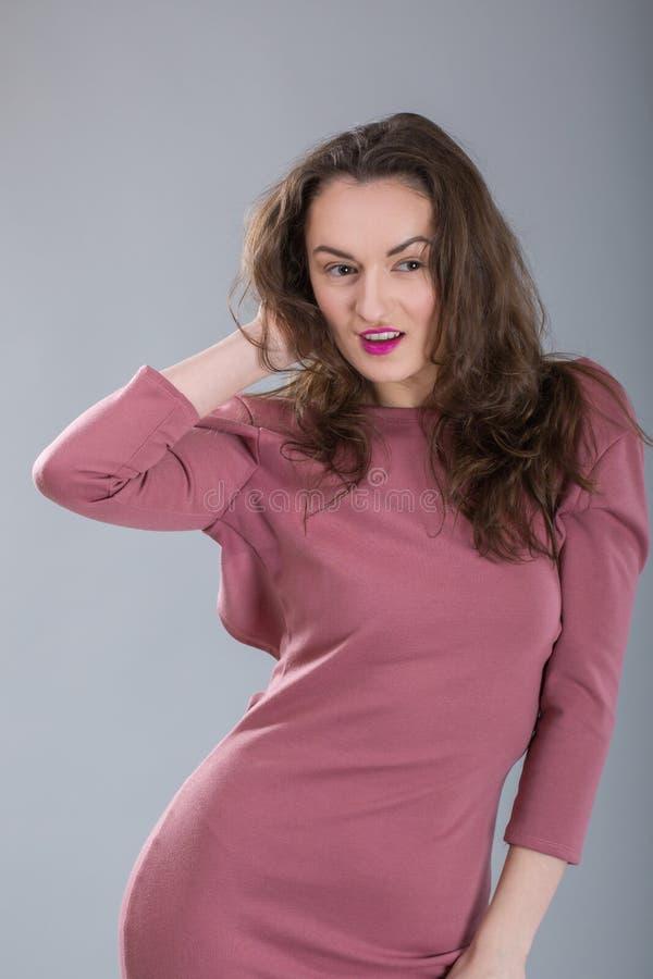Den trendiga kvinnan med långt brunetthår och den röda nätta le lyckliga framsidan i stilfulla rosa färger klär i studio på grå b arkivfoton