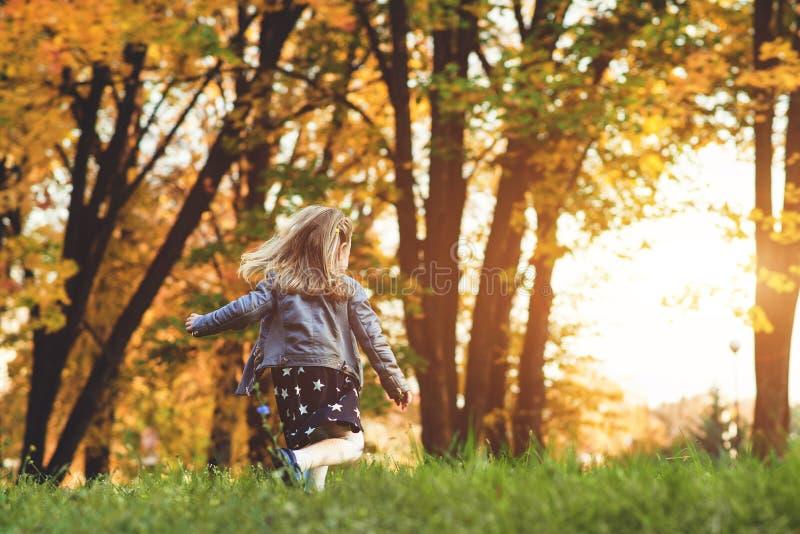Den trendiga lilla flickan som kör i höst, parkerar lyckligt barn utomhus Höstungemode Höstferier kopiera avstånd härligt royaltyfri bild