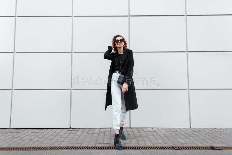 Den trendiga moderna unga hipsterkvinnan i stilfull kläder i läderskor med en handväska i stilfull solglasögon står arkivbild