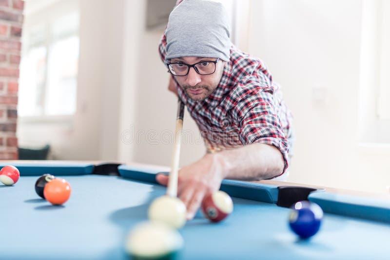 Den trendiga stads- mannen som spelar biljard för pöltabell, spelar fotografering för bildbyråer