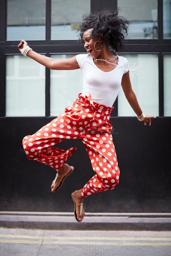 Den trendiga unga kvinnan hoppar upp och skratt, full längd arkivfoton