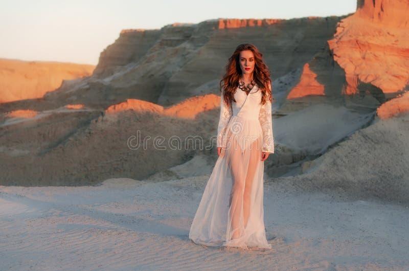 Den trendiga unga kvinnan i en vit lång klänning står i sanden på en bakgrund av kanjonen på solnedgången Boho stil öken arkivfoto