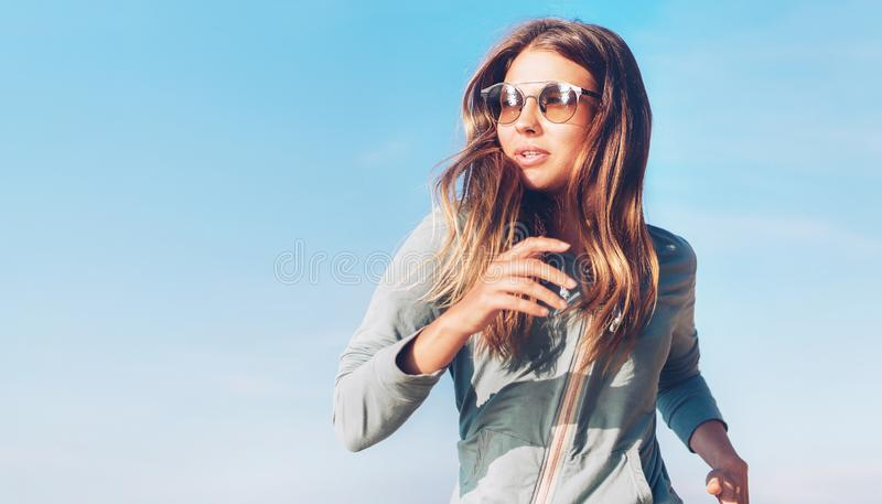 Den trendiga unga longhaired kvinnan har morgonen som joggar p? kusten f?r det lugna havet royaltyfri fotografi
