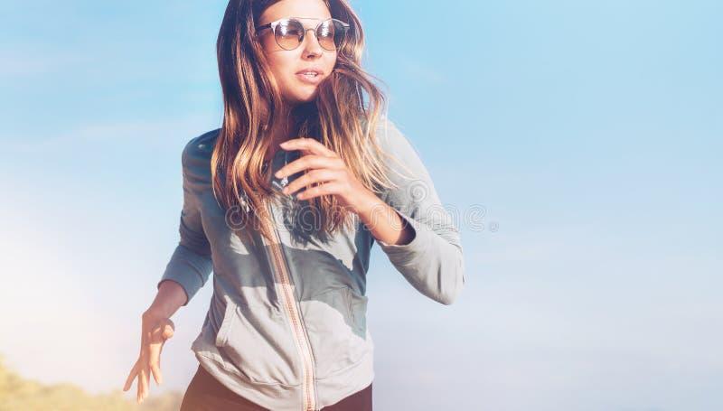 Den trendiga unga longhaired kvinnlign har morgonen som joggar på kusten för det lugna havet royaltyfria bilder