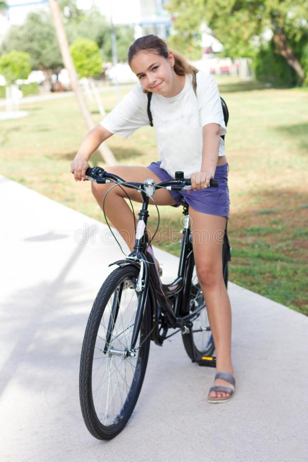 Den trendiga unga tonåriga flickan i kortslutningar och t-skjorta rider en cykel i en sommar parkerar royaltyfria bilder