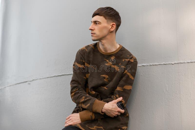 Den trevliga allvarliga unga mannen i en stilfull grön militär trendig frisyr för skjorta c vilar nära den gråa väggen för metall royaltyfri fotografi