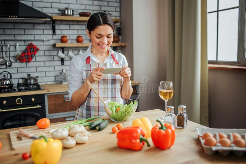 Den trevliga attraktiva kvinnan sitter på tabellen i kök Hon rymmer den vita telefonen och ser den Model leende Hon har grönsaker royaltyfri foto