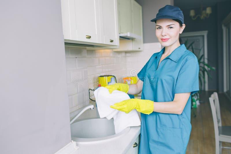 Den trevliga brunetten står på vasken och rymmer den vita handduken Hon ser kameran med förtroende Flickan bär det blåa locket oc royaltyfri fotografi