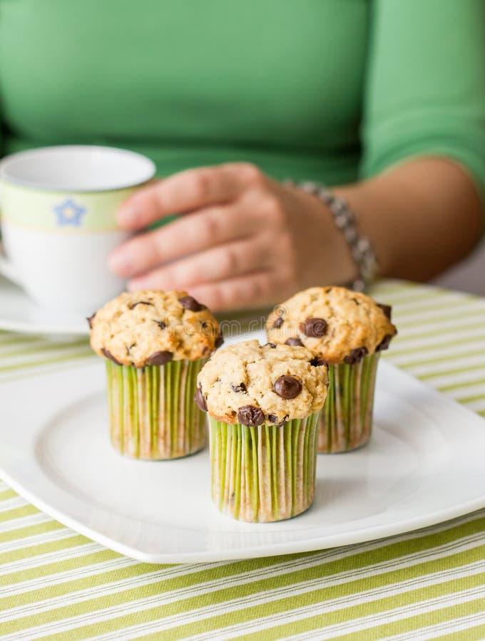 Den trevliga flickan med en kupa och choklad gå i flisor muffinen på frukosten arkivfoton
