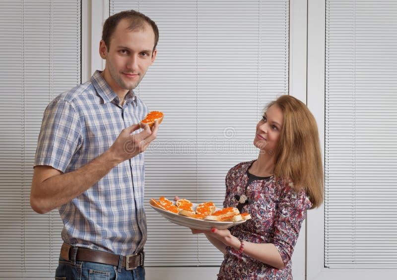 Den trevliga flickan med smörgåsar behandlar den unga mannen arkivfoto
