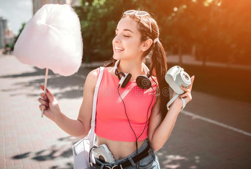 Den trevliga flickan poserar Hon är den hållande sockervadden i en hand och kamera i annan Också finns det hörlurar arkivfoton