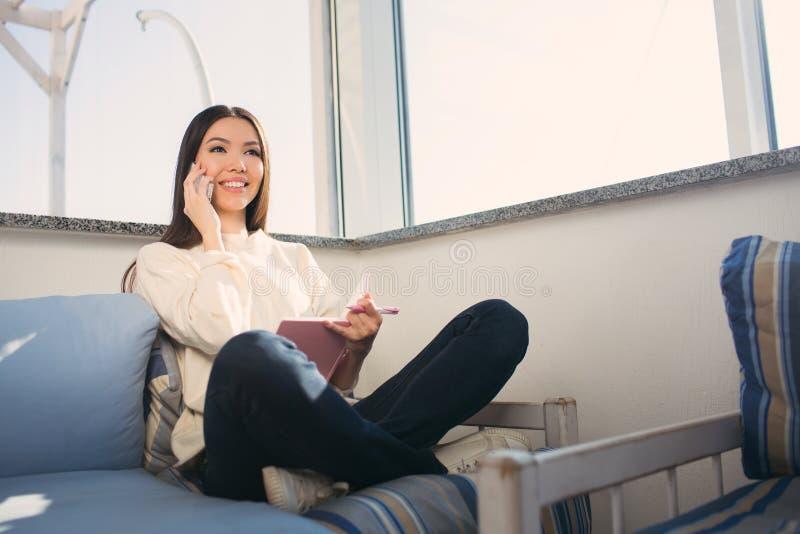Den trevliga flickan sitter på soffan med henne korsade ben Hon talar på telefonen och le Flickan har en anteckningsbok och ett a arkivbilder