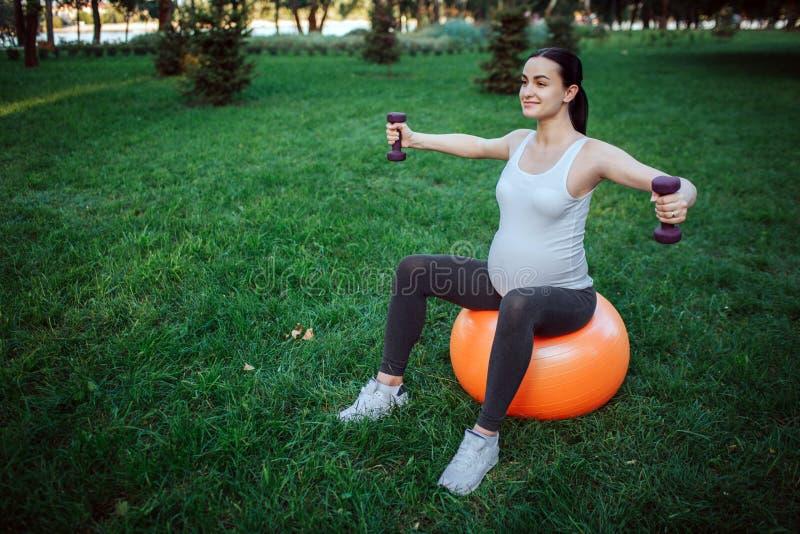 Den trevliga gladlynta unga gravida kvinnan sitter på orange konditionboll i parl Hon övar med hantlar arkivfoton