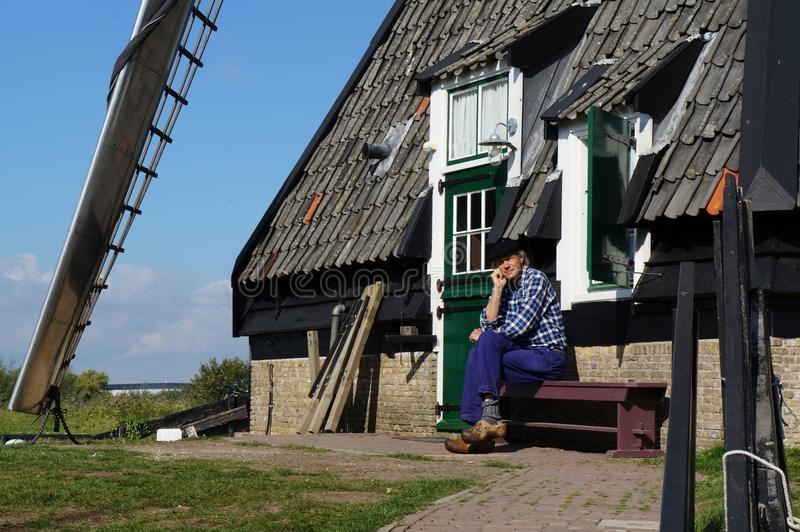 Den trevliga härliga mjölnaren sitter nära hans väderkvarn fotografering för bildbyråer