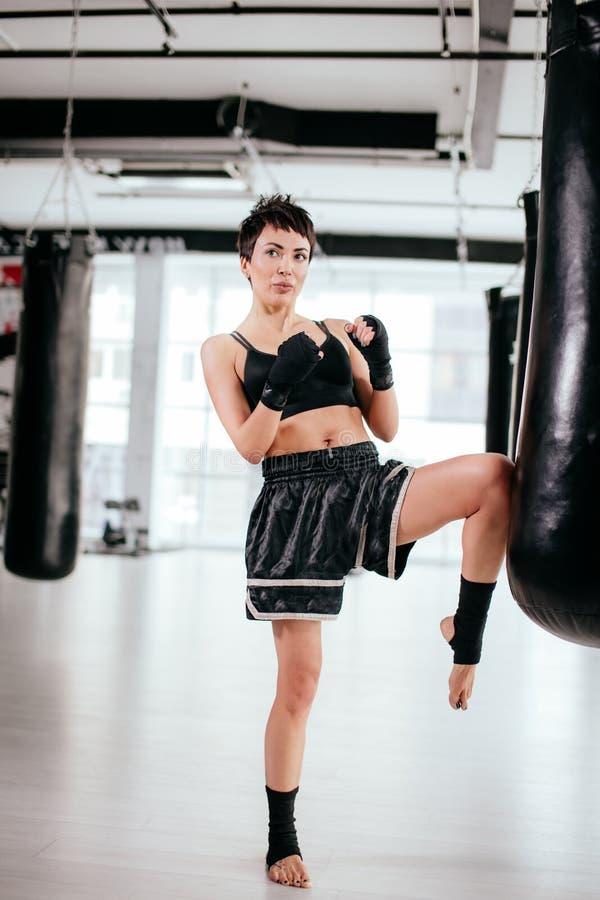 Den trevliga idrottskvinnan ser bort med böjelsebenet royaltyfri foto