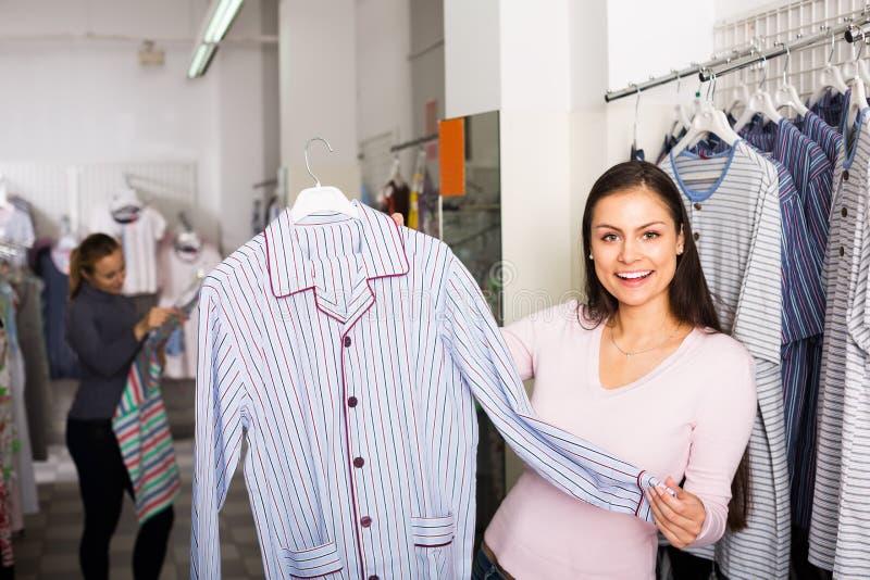 Den trevliga kvinnan som väljer pyjamasöverkanten för man shoppar in royaltyfri foto