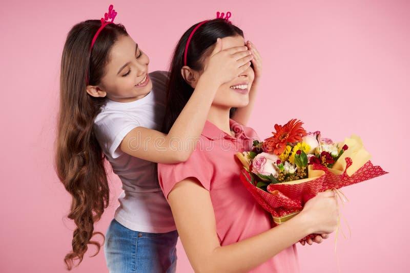 Den trevliga lilla dottern ger blommor till härligt arkivfoto