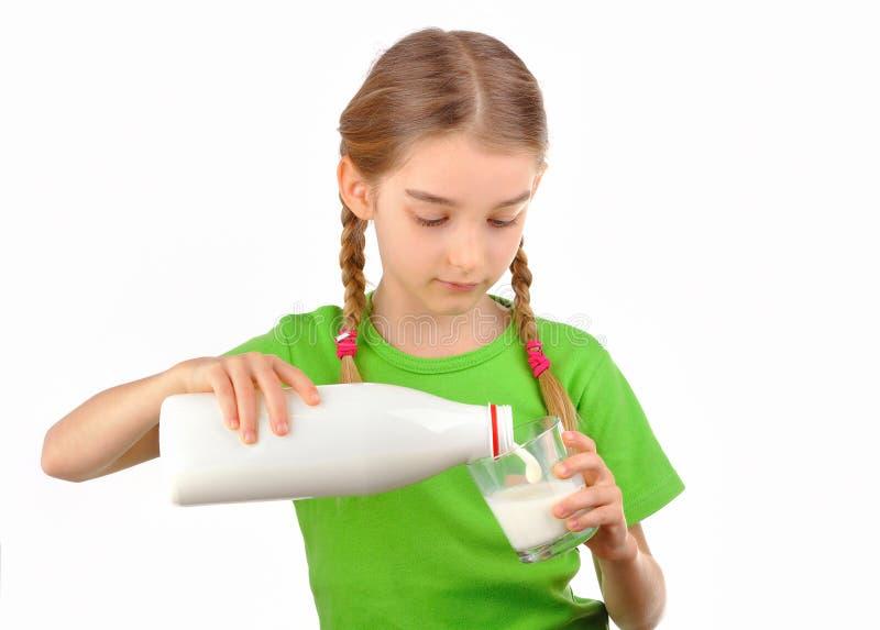 Den trevliga lilla flickan häller mjölkar från en flaska in i exponeringsglas royaltyfri fotografi