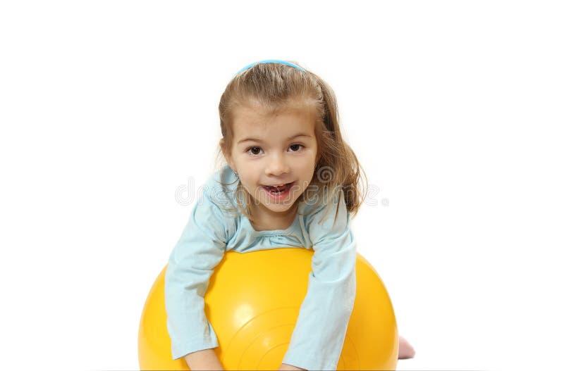 Den trevliga lilla flickan med en stor boll royaltyfri foto