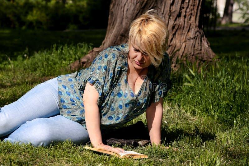 Den trevliga modekvinnan ligger på grönt gräs, och läsa en intressant bok i stad parkera på sommardagen royaltyfria bilder