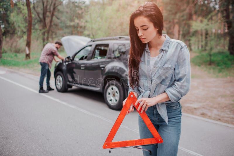 Den trevliga och allvarliga flickan står på vägen och innehavet den röda triangeln för teckenpf Hon ser ner Grabben står royaltyfri fotografi