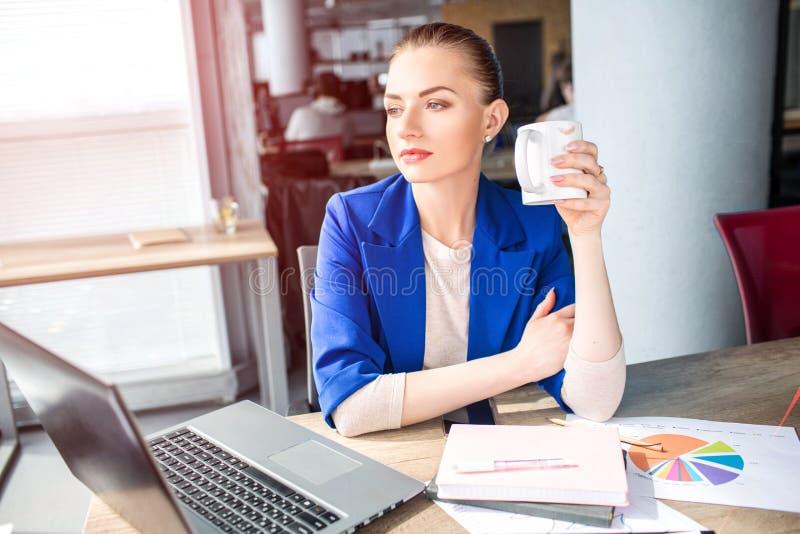 Den trevliga och attraktiva flickan sitter på tabellen och dricker te Hon ser till fönstret och att drömma Denna vuxen människa h arkivbilder