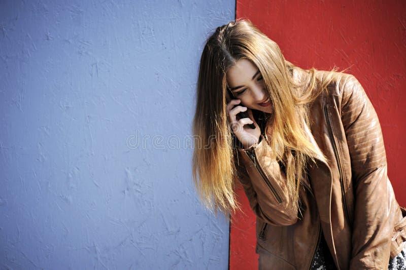 Den trevliga och attraktiva unga hipsterkvinnan pratar på hennes mobil framme av en färgrik bakgrund arkivbild