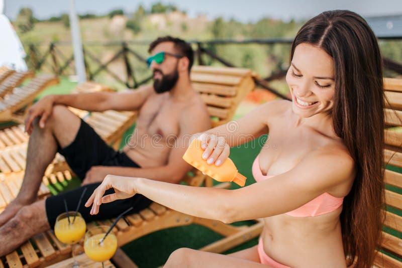 Den trevliga och positiva flickan sitter och sätter någon sunproofkräm på hud Hon rymmer den orange flaskan i assistent Grabben ä royaltyfria foton
