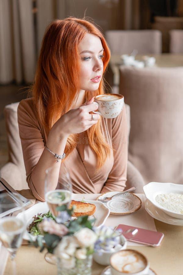 Den trevliga rödhårig mankvinnan äter frukosten i kafé Stående av ungt charmigt kvinnligt dricka kaffe och den rostade smör royaltyfria foton