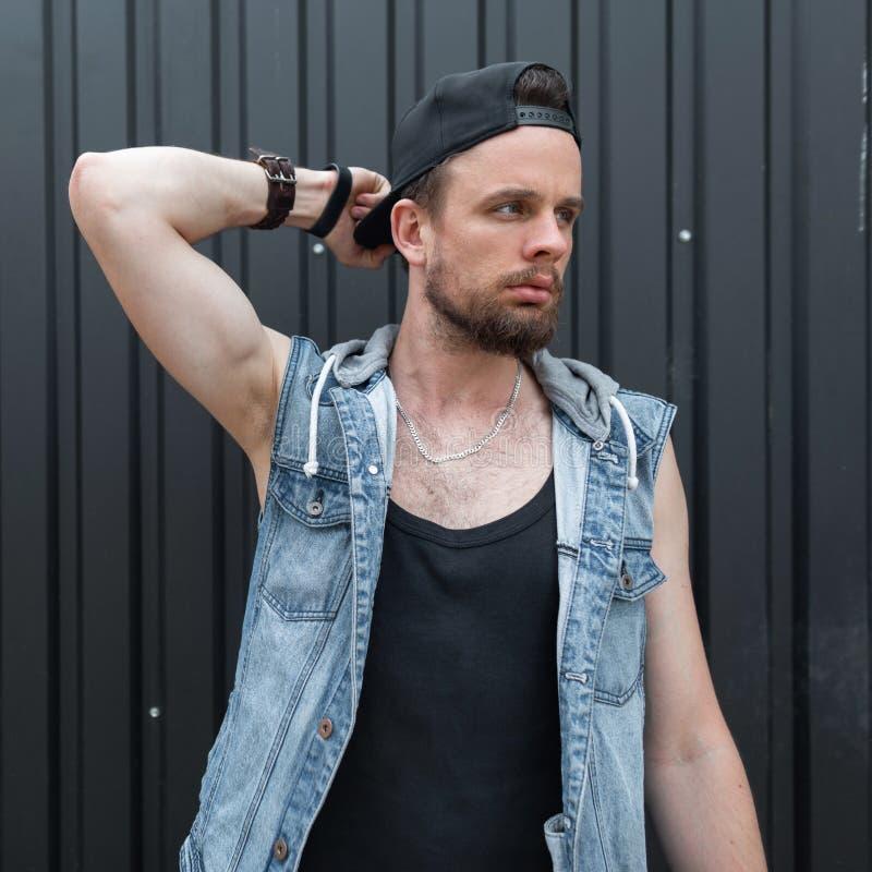 Den trevliga unga mannen som hipsteren med ett skägg i ett stilfullt svart lock i en trendig blå grov bomullstvill tilldelar en m royaltyfria bilder
