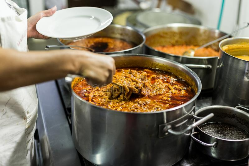 Den Trippa komagen lagar mat i en stor kruka royaltyfri fotografi