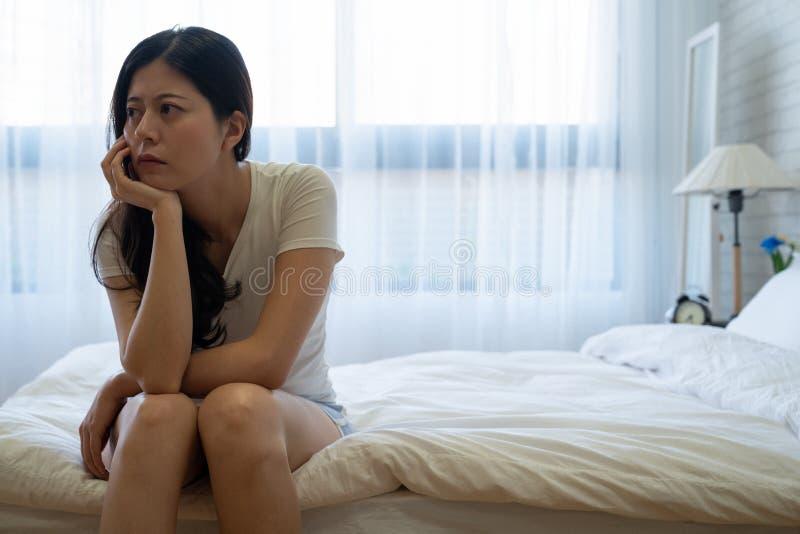 Den tryckta ned kvinnan på säng betraktar om problem arkivfoto