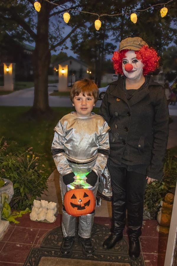 Den Tulsa Oklahoma modern klädde som clownen och sonen som kläddes som astronauttrick r som behandlar på allhelgonaafton royaltyfria bilder
