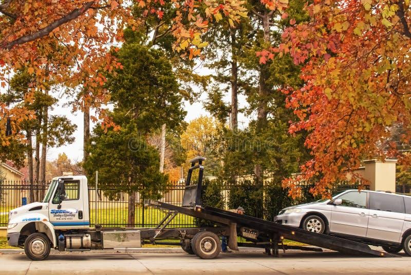 Den Tulsa USA bärgningsbilen med operatören som gör justeringar en skåpbil, laddas på släpet på gatan på ett härligt och färgrikt fotografering för bildbyråer