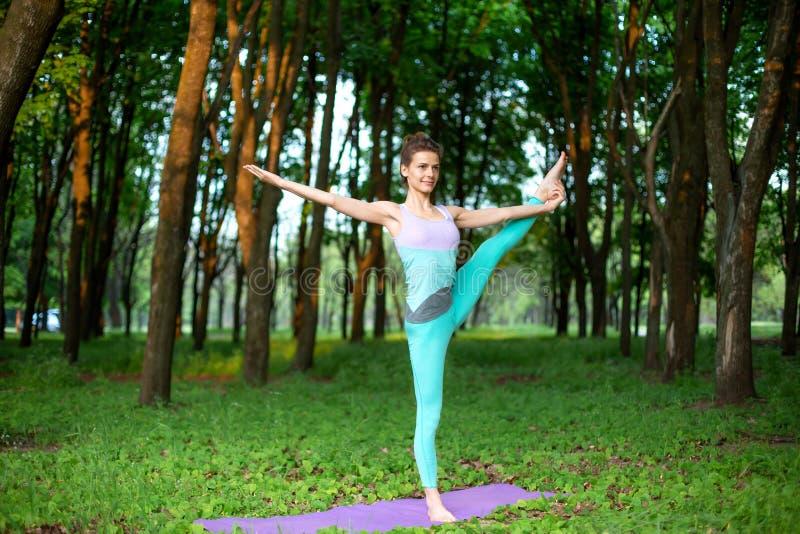 Den tunna brunettflickan spelar sportar och utför härligt, och sofistikerad yoga poserar i en sommar parkerar Kvinna som gör Utth royaltyfri bild